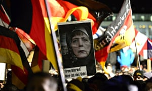 Pegida protesters holding a poster featuring German chancellor Angela Merkel wearing a hijab and a s