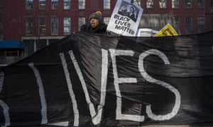 A demonstrator holds a banner during a protest against police violence towards minorities.