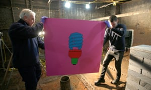 Art movers carry Michael Craig-Martin's acrylic on aluminium picture of a lightbulb, in the former Laurie Grove Baths