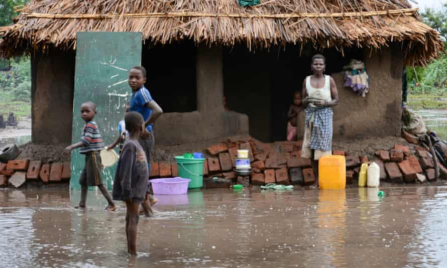 A family wait outside their home for relief teams in the district of Chikwawa, near Blantyre.