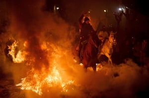 Riders are spurring their horses through a bonfire