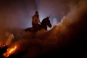 A man rides a horse through a bonfire during 'Las Luminarias'