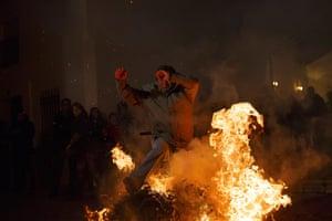 A man jumps through a bonfire