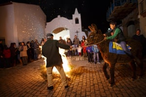 A boy sits on top of a donkey being pulled around a smaller bonfire by a man