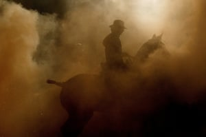 The silhouette of a man on horseback is seen through the smoke