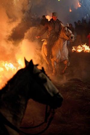 A man rides a horse through a bonfire