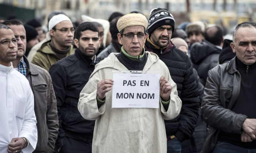 A Muslim man holds a placard reading 'Not in my name' near the mosque of Saint-Étienne, eastern France, on 9 January.