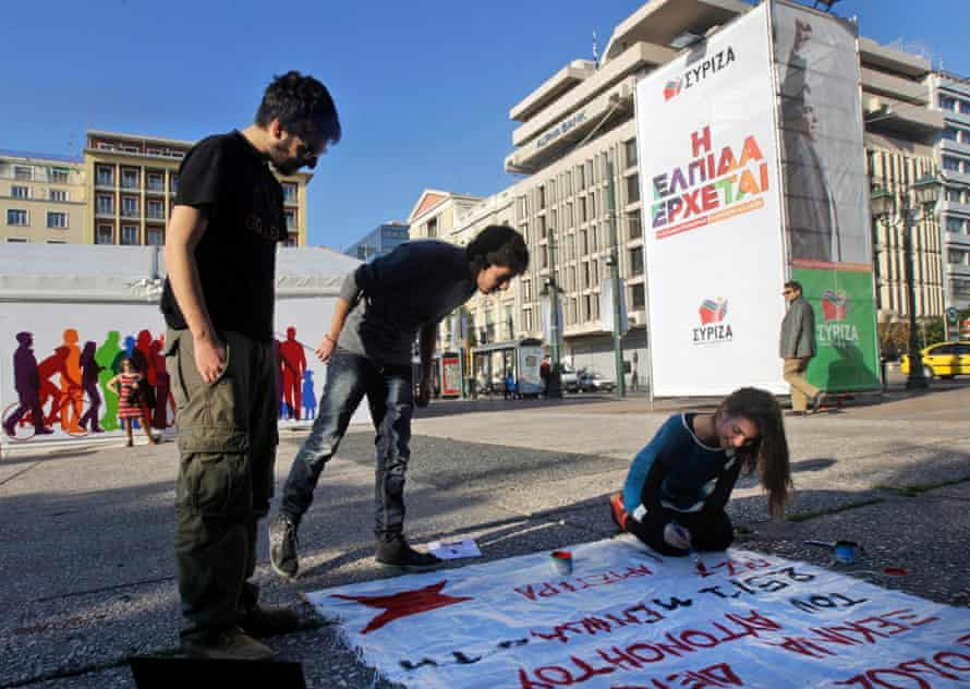 Syriza supporters paint a banner outside anelection rally in central Athens.