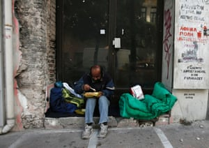 homeless man eats doorway closed shop Athens.