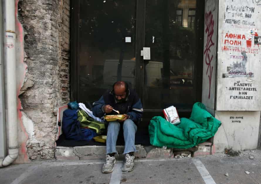 homeless man eats doorway closed shop Athens.