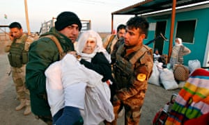 Peshmerga soldiers assist one of the Yazidi prisoners released by Islamic State