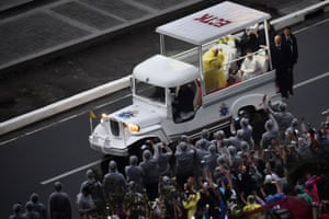 Pope Francis waves to the crowd from  his popemobile based on the design of a jeepney.