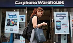 Woman walks past a branch of Carphone Warehouse