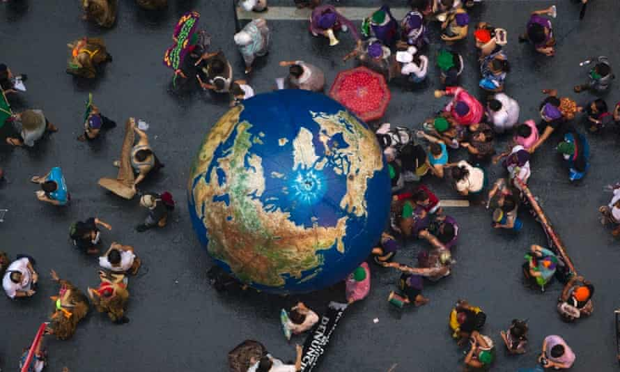 """Activists push an inflatable globe during a """"Global March"""" as part of the People's Summit for Social and Environmental Justice in Defense of the Commons, a parallel event during the UN Conference on Sustainable Development, or Rio+20, in Rio de Janeiro, Brazil, June 20, 2012."""