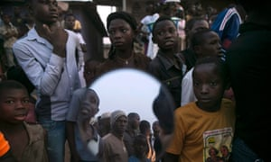 Bystanders, some reflected in a mirror, watch as the body of a suspected Ebola victim lies on a street in the town of Koidu, Kono district in Eastern Sierra Leone December 18, 2014.