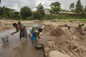 Women collects sand in a stream caused by flood in malawi