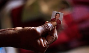 A woman holds a picture of her husband