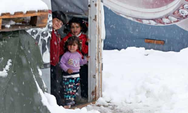 Syrian refugee children stand inside a tent at a refugee camp in Zahle, Lebanon