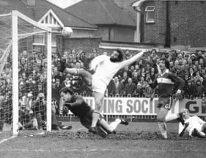 Middlesbrough keeper Pat Cuff scrambles at the feet of Wimbledon striker Roger Connell as the ball soars over the bar during their goal-less draw at Plough Lane in 1977=