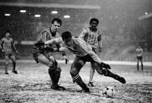 Watford's John Barnes evades Coventry City defender Trevor Peake as both players attempt to cope with the snow during Watford's 3-1 win