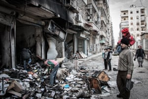 Aleppo, Syria A man carrying his daughter and looking at the devastation after a rocket attack by regime forces