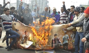 Protester burn a poster of the film PK outside a cinema in Ghaziabad, India