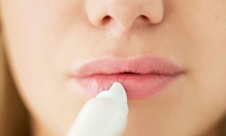A girl applies lip balm