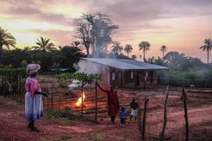 Villagers talk outside a house as the sun sets