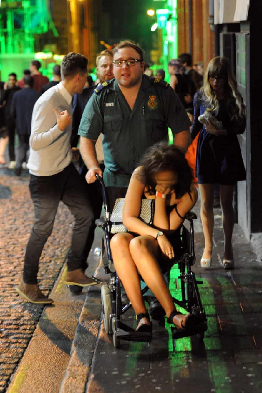 A worse-for-wear reveller is pushed to an ambulance on a wheelchair in the early hours of New Year's Day in Concert Square, Liverpool.