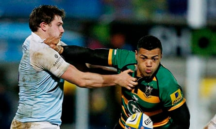 Adam Powell of Newcastle Falcons tries to halt a charge by Luther Burrell of Northampton Saints