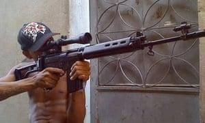 A man armed with a sniper's rifle in Vila Aliança.