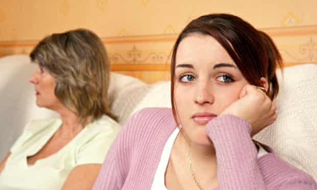 Teenager next to her mother, looking away unhappily
