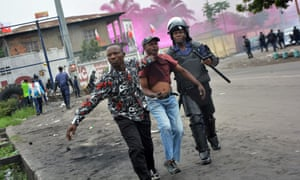 A demonstrator is arrested following clashes with police in Kinshasa