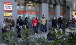 People wait in line at a government employment office on Paseo de las Acacias in Madrid on December 2, 2014.