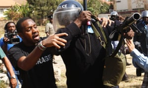 Kenyan activist Boniface Mwangi tries to help a riot police officer injured in a scuffle during protests against the walling off of the playground.