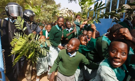 Pupils from Lang'ata road primary school run past riot police as they try to reclaim their playground.