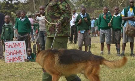 Schoolchildren face off against a police dog handler.