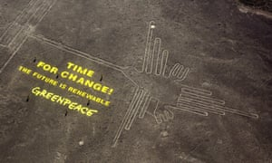 Greenpeace activists stand next to large letters that spell out 'Time for Change: The Future is Renewable' next to the hummingbird geoglyph in Nazca, Peru in December.