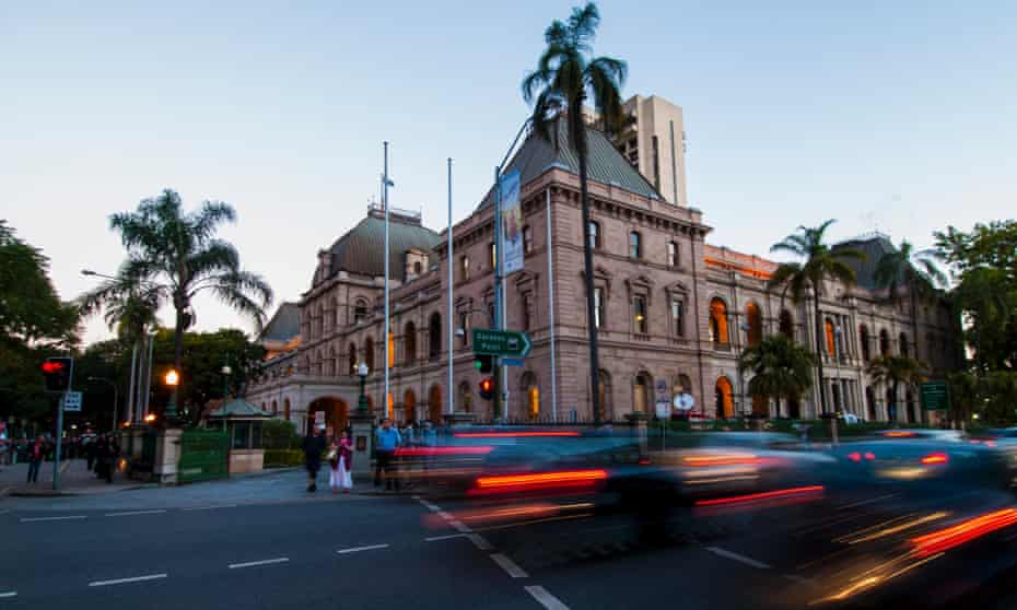 Cars drive past Queensland's Parliament House in Brisbane