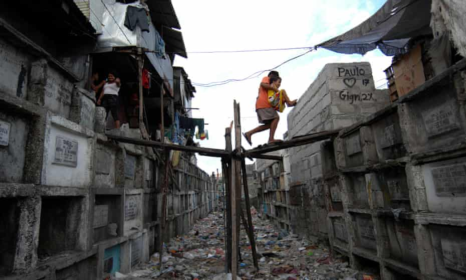 Filipino children walk between the tombs of the Municipal Cemetery of Navotas, north of Manila, where they live.