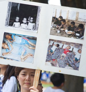 A woman holds up a poster with photos from an internment camp in North Korea during a White House vigil in Washington DC in 2012.