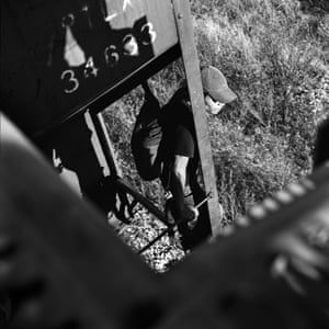A Guatemalan migrant rides between two boxcars on a cargo train, Oaxaca