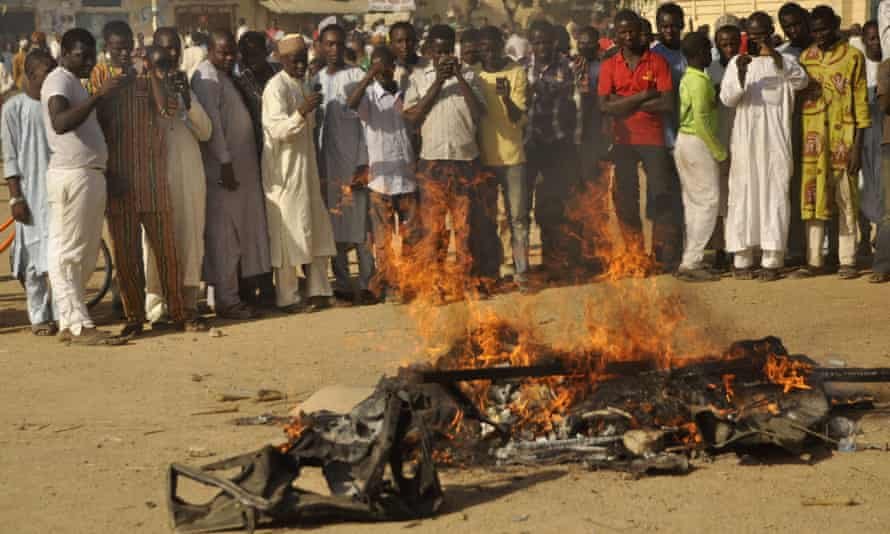 People gather at the site of a bomb explosion in a area know to be  targeted by the  militant group Boko Haram,  in Kano, Nigeria.
