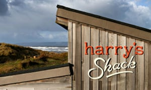 The wooden shed-like Harry's Shack with the sea behind and a stormy sky