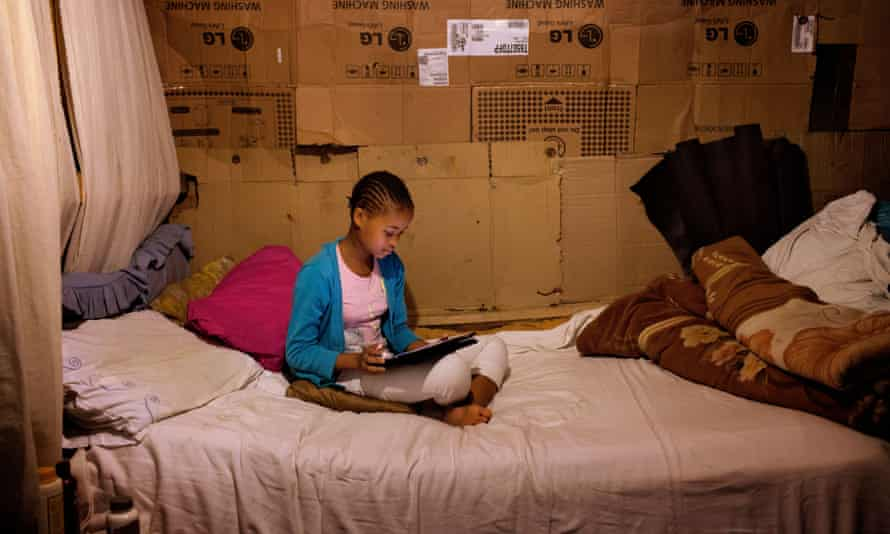 Phelela, 13 years old, doing homework on an iPad in her bedroom in Nyanga, Cape Town, South Africa.