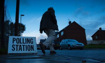 Man walking past polling station sign