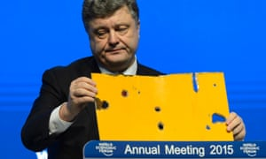 The president of Ukraine Petro Poroshenko speaks with a piece of a damaged passenger bus hit by a shell that killed twelve passengers and injured 13 others at a Ukrainian military checkpoint near the town of Volnovakha, during a panel session today.