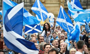 Yes campaigners wave Scottish flags at a pro-independence rally the day before the referendum