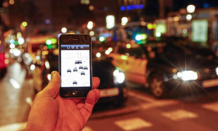 A smartphone user with the Uber app on Paseo de Gracia in Barcelona.