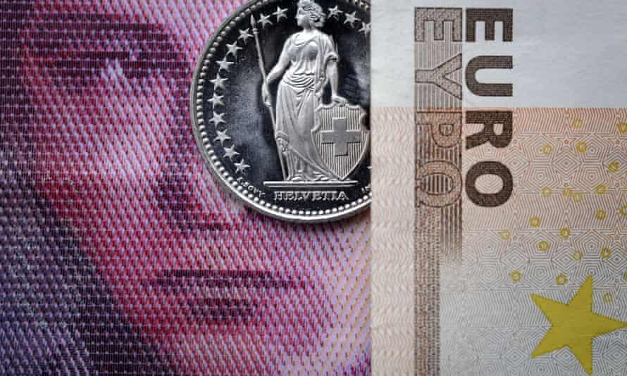 A Swiss coin is seen beneath a euro banknote,